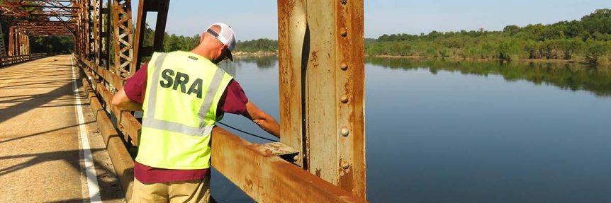 Man monitoring water quality from bridge