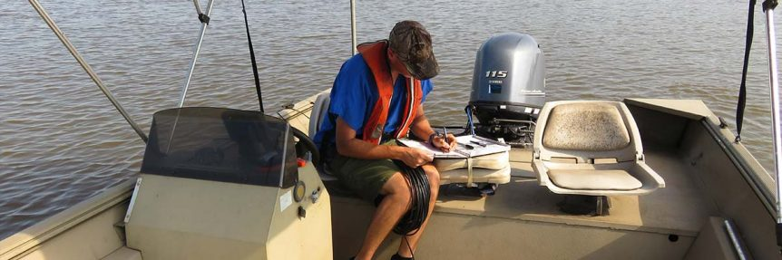 Man filling our report in boat on the water